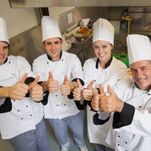 kitchen with happy chefs showing thumbs up